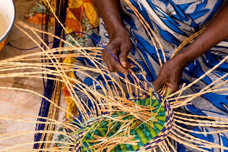 Eine ghanische Frau knüpft einen Krob aus Elefantengras.